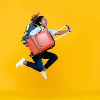 Excited African American woman tourist woman with backpack and luggage jumping in mid-air studio shot isolated on colorful yellow background